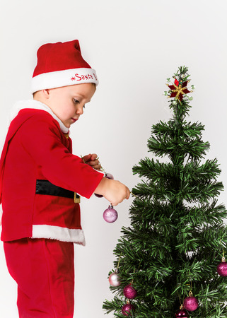 Baby boy dressed as Santa Claus decorating  Christmas tree, hanging ornaments.