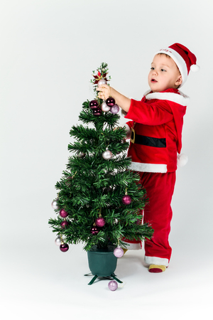 Baby boy dressed as Santa Claus decorating  Christmas tree, hanging ornaments.  photo