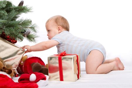 Baby boy reaching for Christmas gifts. Studio shoot on white .