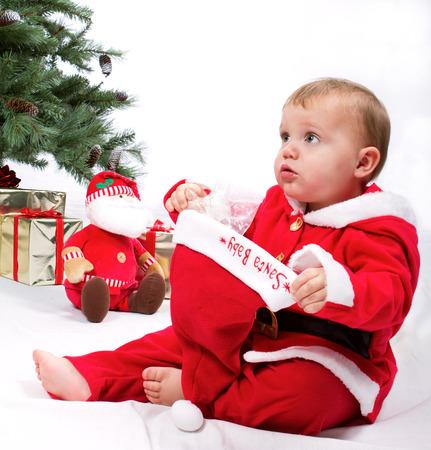 Santa Baby boy sitting next to Christmas tree. Studio shoot on white . Stock Photo