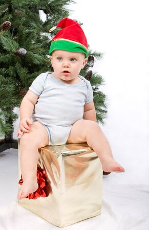 Baby boy sitting on Christmas gift. Studio shoot on white . Stock Photo