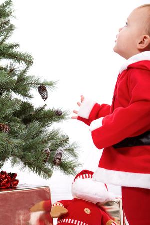 Santa Baby boy standing next to Christmas tree. Studio shoot on white .