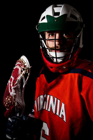 Lacrosse player wearing helmet and holding stick. Studio shoot on the black . Stock Photo