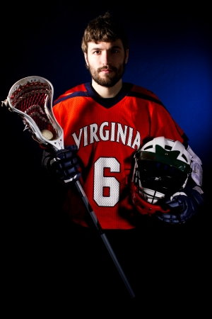 Lacrosse player holding helmet and stick. Studio shoot on the black with blue light spot.
