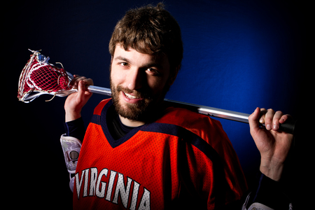 Lacrosse player holding stick. Studio shoot on the black with blue light spot.