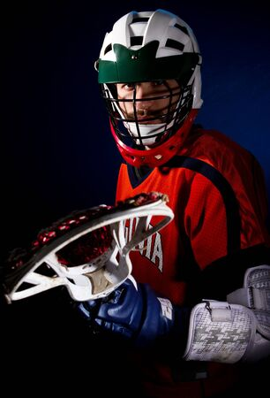 Lacrosse player wearing helmet and holding stick. Studio shoot on the black with blue light spot.