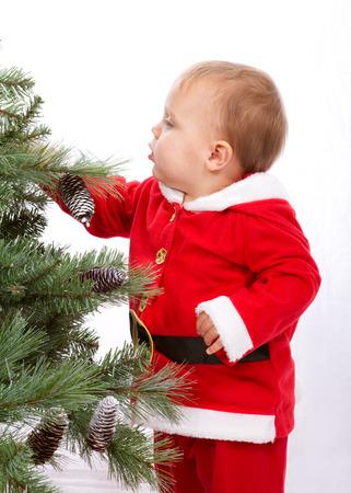 Santa Baby boy standing next to Christmas tree. Studio shoot on white background. Stock Photo
