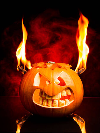Evil face of Halloween pumpkin with flames and red smoke in the background. Stock Photo
