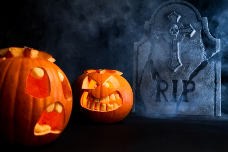 Angry face and scared face of Halloween pumpkins with tombstone on misty dark background.