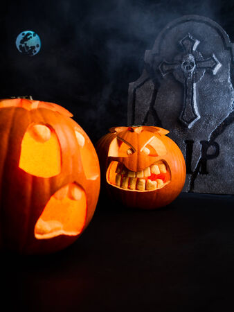 Angry face and scared face of Halloween pumpkins with moon and tombstone on misty dark background.