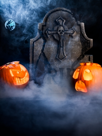 Angry face and scared face of Halloween pumpkins with moon, tombstone and bat on misty dark background.