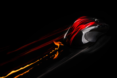 PC mouse in fast motion with flames and light trails. Single object on black background.