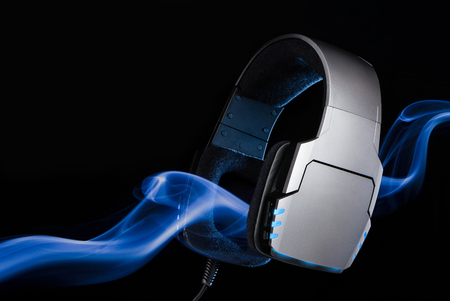 Silver large headphones with stream of blue smoke. Single object on black background.