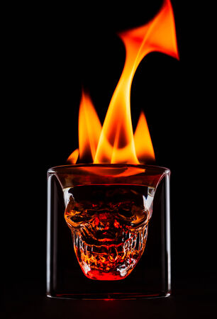Skull shape glass with flames on the top. Single object on black background.