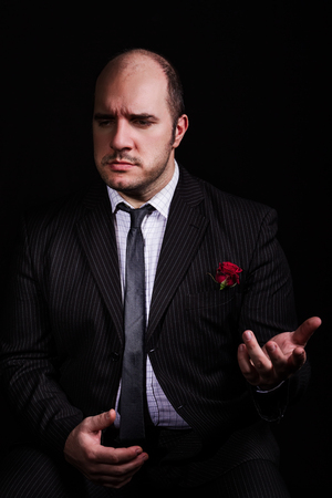 Portrait of man, godfather-like character. Studio shpt, black background.