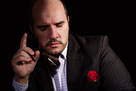 Portrait of man, godfather-like character. Studio shot, black background. Stock Photo