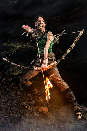 Rise of the Tomb Raider. screaming woman dressed up as Lara Croft holds a bow and pulls the bowstring with a burning arrow. Stock Photo