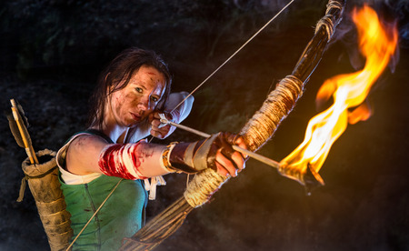 Rise of the Tomb Raider. Woman dressed up as Lara Croft aiming with a bow and pulls the bowstring with a burning arrow. Stock Photo