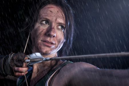 Rise of the Tomb Raider. Woman dressed up as Lara Croft stands in the rain, aiming with a bow and pulling the bowstring with a arrow.