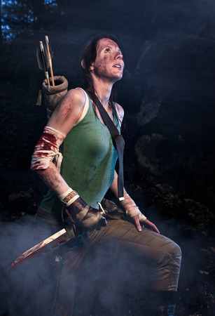 Rise of the Tomb Raider. Woman dressed up as Lara Croft stands next to the caves, holging a knife in the hand. Wears a quiver with arrows on her back.