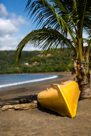 Yellow boat laying down next to the palm tree on Playa Del Coco, Costa Rica.