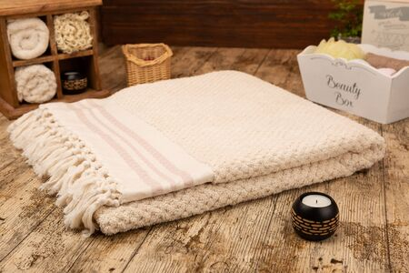 Large handwoven cotton bath towel on wooden background surrounded by bathroom props Stok Fotoğraf