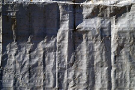 Minimal view of a gray tarpaulin in sidelight with strong shades Фото со стока