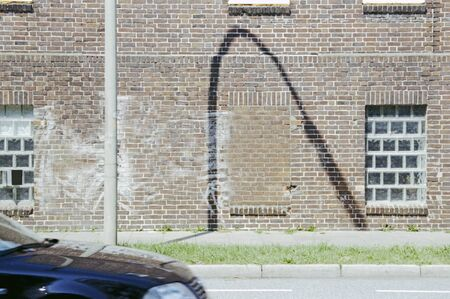 Photograph of the shade of a lamp on a brick wall with a car, passing by