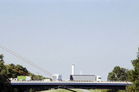 Photography of trucks and cars, passing a highway bridge on a sunny summer day.