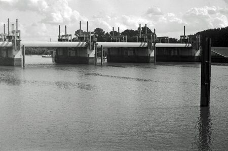 Black and white analogue photography of a suburban industrial landscape at a river with industrial buildings.
