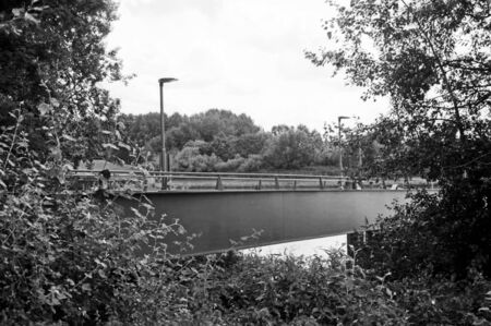 Black and white analogue photography of a metal bridge on a river with street lights. Stock Photo