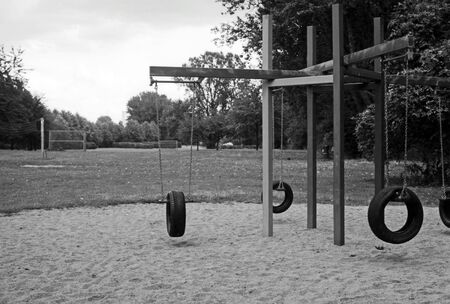 Black and white portrait of a couple having fun on a playground in a park on a summer day.