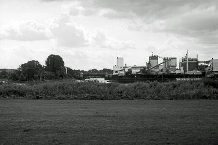 Black and white analog photography of a scenic view of an industrial landscape, photographed from a park behind a river.