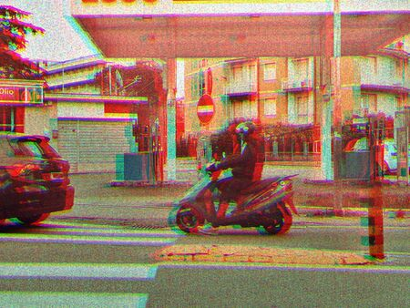 Photography of a scooterist passing a gas station on a scooter. 免版税图像
