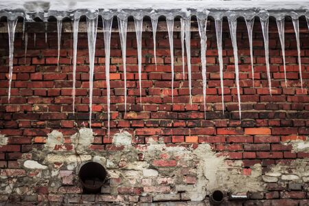 Icicles above the old brick wall at winter Stock Photo