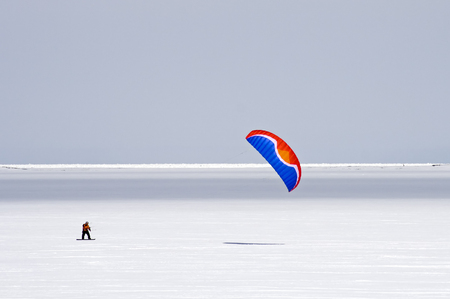 kiting: colored kite on ice in winter