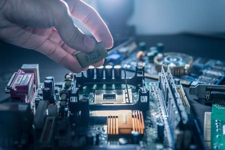 De technicus plaatst de CPU op de socket van het moederbord van de computer.