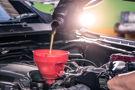 het close-up beeld van de technicus die een nieuw smeermiddel in de motor van de auto vult. het concept van automotive, reparatie, mechanica, voertuig en technologie.