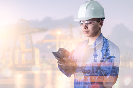 the double exposure image of the engineer using a smartphone overlay with oil refinery image.The concept of modern life, engineering, construction and internet of things.