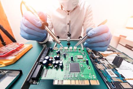 De Aziatische technicus die het moederbord herstelt door in het laboratorium te solderen. het concept van computerhardware, mobiele telefoon, elektronisch, reparatie, upgrade en technologie. Stockfoto