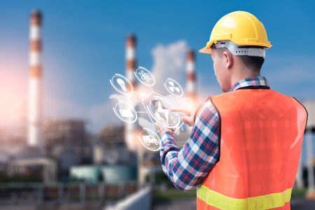 The abstract image of the engineer holding smartphone with hologram and the blurred power plant is backdrop. the concept of clean energy, futuristic, industrial4.0 and internet of things.
