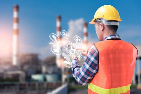 Het abstracte beeld van de ingenieur die smartphone met hologram vasthoudt en de wazige elektriciteitscentrale is de achtergrond. het concept van schone energie, futuristisch, industrieel4.0 en internet der dingen.