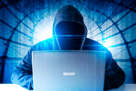 The abstract image of the hacker using a laptop overlay with source code hologram image. the concept of cyber attack, virus, malware, illegally and cyber security. Stock Photo