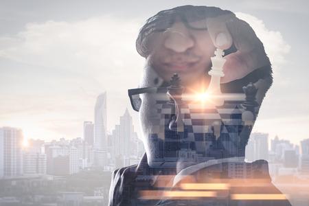 Das Doppelbelichtungsbild des Geschäftsmanndenkens überlagert mit Schachspiel und Stadtbildbild. das Konzept von Strategie, Planung, Management, Intelligenz und Bildung.