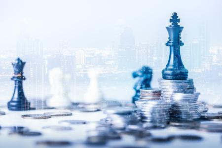 zdjęcie stosu monet z podwójną ekspozycją, na którym znajduje się zestaw szachowy Staunton, taki jak król, i nałożony na obraz pejzaż miejski. pojęcie rachunkowości, biznesu, finansów, ekonomii i inwestycji. Zdjęcie Seryjne