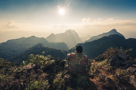 the hiker sitting on the cliff for looking to the sun and layer of mountains. Doi luang chiang dao, Chiang dao national park, Chiang mai, Thailand. Фото со стока