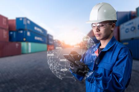L'immagine astratta dell'ingegnere indica l'ologramma sul suo smartphone e il cortile del container sfocato fa da sfondo. il concetto di rete di comunicazione internet delle cose e logistica. Archivio Fotografico