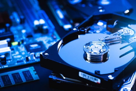 The abstract image of inside of hard disk drive on the technicians desk and a computer motherboard as a component. the concept of data, hardware, and information technology.