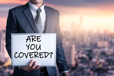 The abstract image of the businessmen hold a whiteboard and text wrote Are you covered? during sunrise overlay with cityscape image. The concept of insurance, business, health care and emergency.