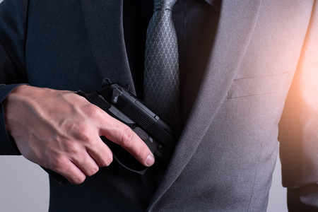 the abstract image of the gunman pull a gun out of his suit. the concept of gangster, firearm, bodyguard, security and business. Banco de Imagens